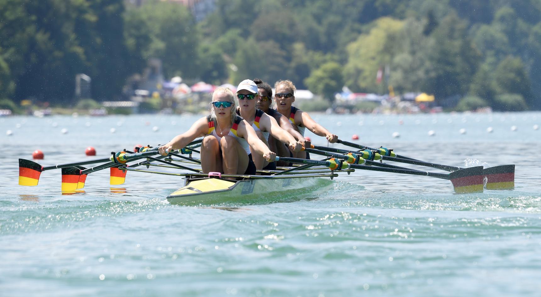 Vier Frauen im Ruderrennboot mit aufgestellten Ruderblättern die in den Nationalfarben Schwarz-Rot-Gold gestrichen sind