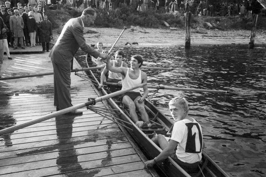 Historisches Bild vom Stadtarchiv Kiel: ein älterer Herr ehrt auf einem Bootssteg einen siegreichen Vierer mit Schülern